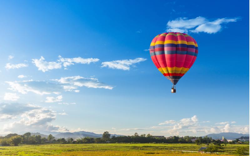 Colourful hot air balloon over a green field