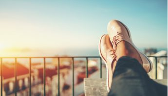 Close up of a woman sitting with their feet up on a balcony