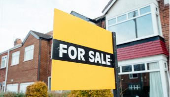 Row of houses with a for sale sign outside